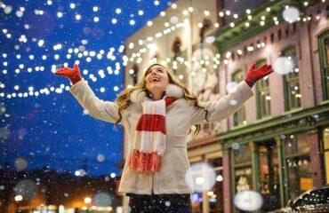 Happy woman under christmas lights