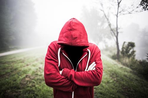 Man looking down in red hoodie