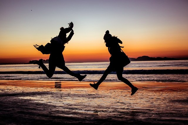 SIlhouetted couple jumping on beach